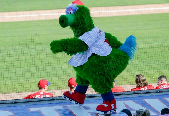 In this Feb. 23, 2020, file photo, the Phillie Phanatic mascot walks on the third-base dugout while the Philadelphia Phillies played the Pittsburgh Pirates in a spring training baseball game in Clearwater, Fla.