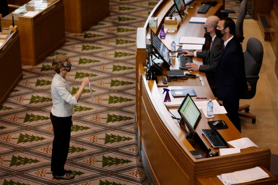 Rep. Nancy Nathanson, D-Eugene, (left) speaks to legislative staff in the House of Representatives during a special session of the Oregon Legislature in the Oregon State Capitol building in Salem, Oregon, on Thursday, June 25, 2020.