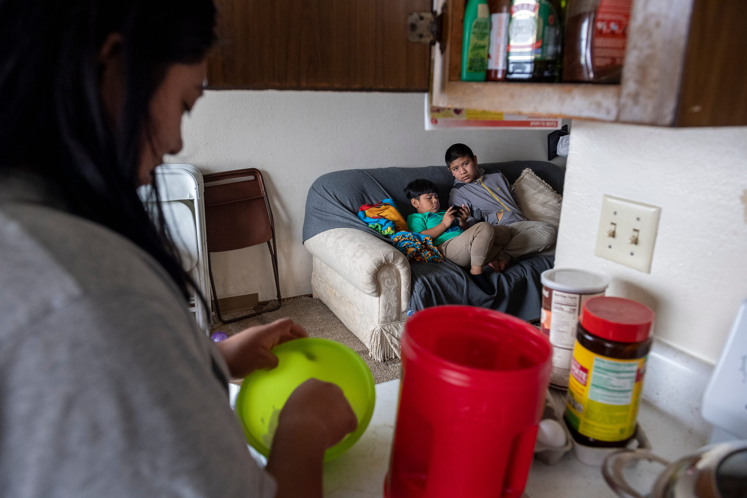 Resi Salvador, left, whisks pancake batter on a Sunday morning as her two younger brothers sit on the couch in Salinas on May 31, 2020.