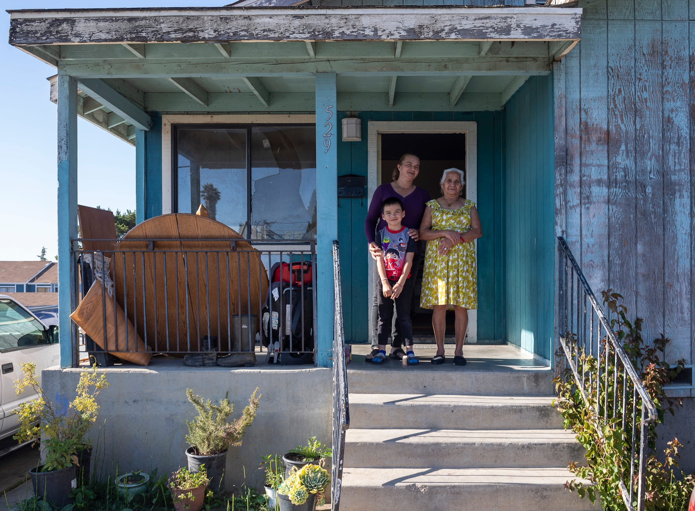 """Eufemia """"Jenni"""" Aguilar, 53, holds her grandson Kender, 6,  next to her mother, Barbara Rodriguez Ramos, 81, in front of the house where they rent one small bedroom. After living with Aguilar and Kender for three months, Ramos moved to Texas with her son."""