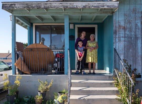 """Eufemia """"Jenni"""" Aguilar, de 53 años, carga a su nieto Kender, de 6, junto a su madre, Bárbara Rodríguez Ramos, de 81 años, frente a la casa donde rentan un pequeño dormitorio. Después de vivir con Aguilar y con Kender durante tres meses, Ramos se mudó a Texas con su hijo."""