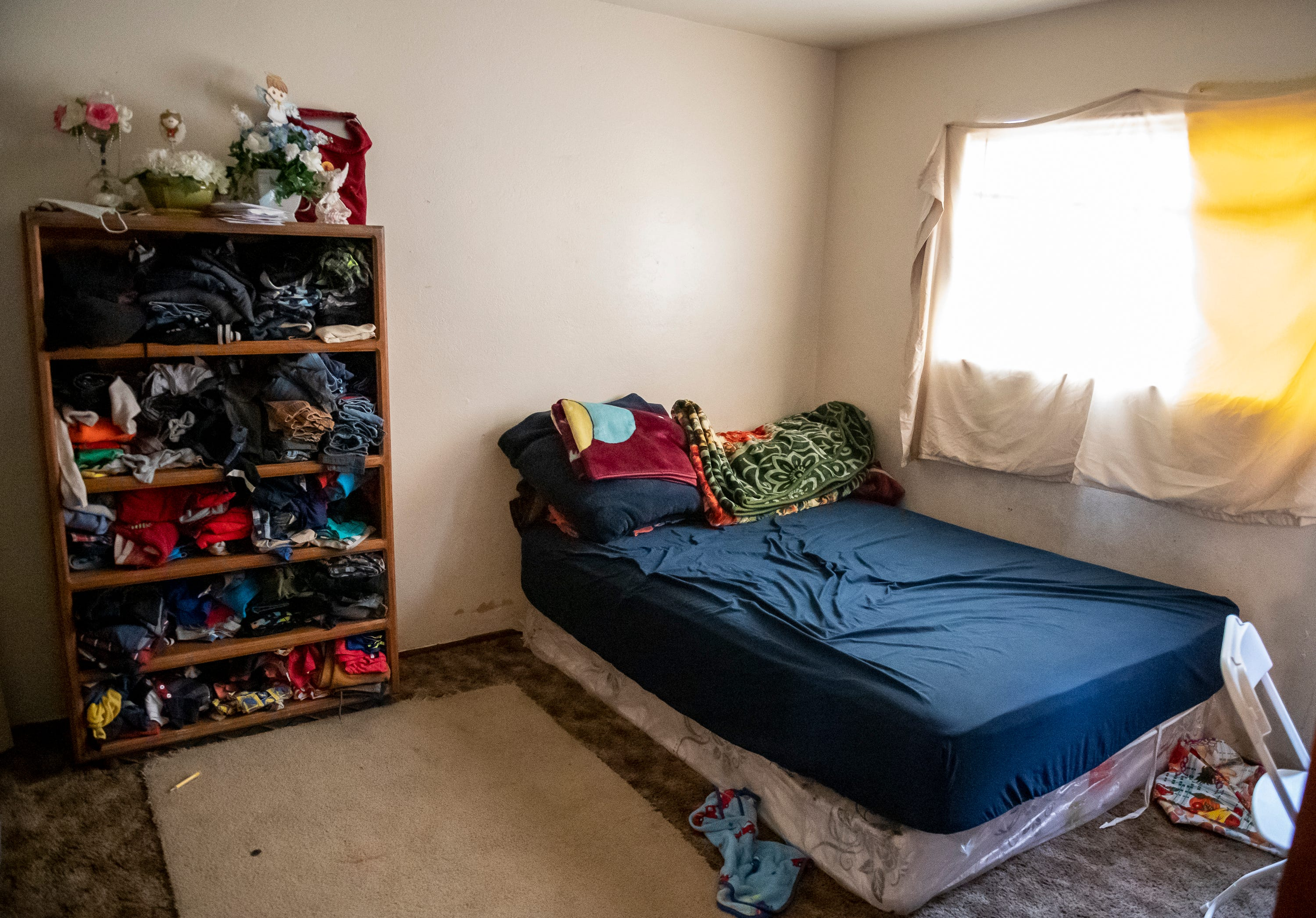 A wooden bookshelf that is used to store most of the clothes worn by the children of the Salvador family stands next to the bed that is used by Resi's mom, dad and her youngest brother Jesus. Like many children of immigrants, Resi has to sleep in the living room with her younger brothers due to her crowded living space.