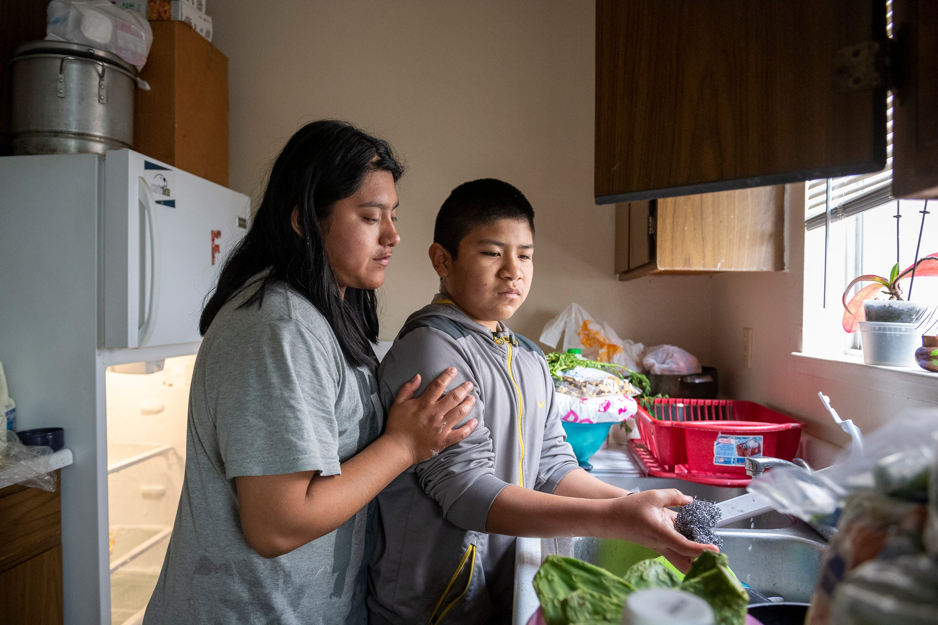 Resi Salvador, 19, left, rests her hand on her brother Aldo's, 11, arm as he washes the dishes to help her clean the house before their parents come home. Resi has three brothers that she takes care of; As the oldest siblings, she and Aldo take on the most household responsibilities.