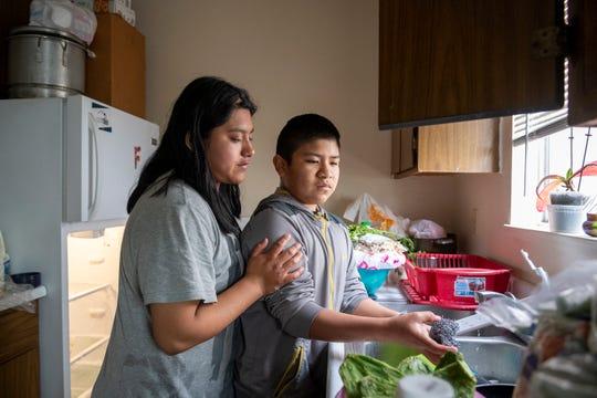 Resi Salvador, de 19 años de edad, a la izquierda, posa su mano sobre el brazo de su hermano Aldo, de 11 años, quien le ayuda a lavar los platos antes de que sus padres lleguen a casa. Resi tiene tres hermanos a los que cuida; ella y Aldo son los mayores y asumen la mayoría de las responsabilidades del hogar.