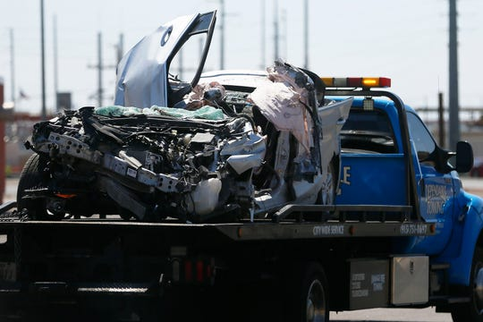 A tow truck takes away part of a 2019 Chevy Cruze that was destroyed in a crash that killed seven people and wounded three early Thursday, June 25, 2020, on the 700 block of West Paisano Drive.