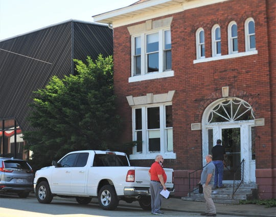 Muskingum Behavioral Health Executive Director Steve Carrel (red) talks to one of the bidders on Thursday. MBH and Fairfield Homes held a pre-bid meeting on the future site of The Pearl House, which will be located at the corner of Third and South streets in downtown Zanesville.
