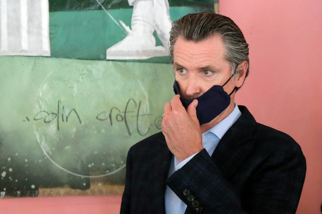 Gov. Gavin Newsom wears a protective mask on his face while speaking to reporters at Miss Ollie's restaurant during the coronavirus outbreak in Oakland, Calif., on June 9, 2020.