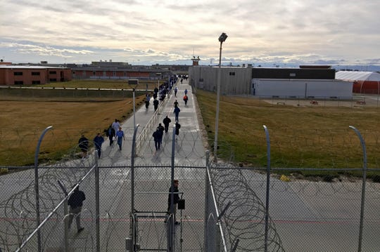 Inmates walk across the grounds of the Idaho State Correctional Institution in Kuna, Idaho, in this Jan. 30, 2018, file photo. Hundreds of thousands of dollars in coronavirus relief payments have been sent to people behind bars across the United States, and now the IRS is asking state officials to help claw back the cash that the federal tax agency says was mistakenly sent.