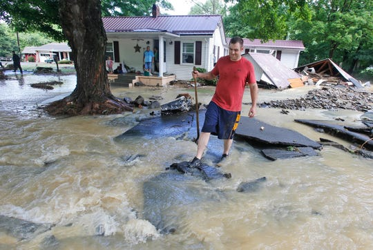 Mark Bowes, of White Sulphur Springs W. Va., makes his way to the road as he cleans up from severe flooding in White Sulphur Springs, W. Va., Friday, June 24, 2016. A deluge of 9 inches of rain on parts of West Virginia destroyed or damaged more than 100 homes and knocked out power to tens of thousands of homes and businesses. (