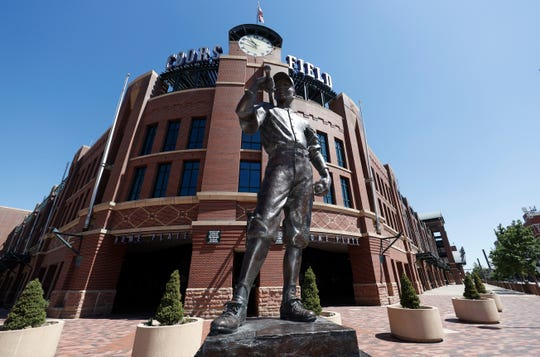 "The bronze statue entitled ""The Player,"" by sculptor George Lundeen, stands in front of the main gate of Coors Field, home of the Colorado Rockies."
