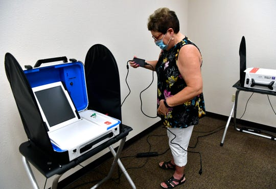Election clerk Carol Taylor holds up a power cord to a voting machine Thursday at the Taylor County Elections Office.