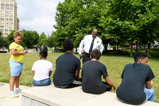 Buncombe County Sheriff Quentin Miller talks to children in a summer program with Christine W. Avery Learning Center, as they stop at McGuire Green to play football June 24, 2020.