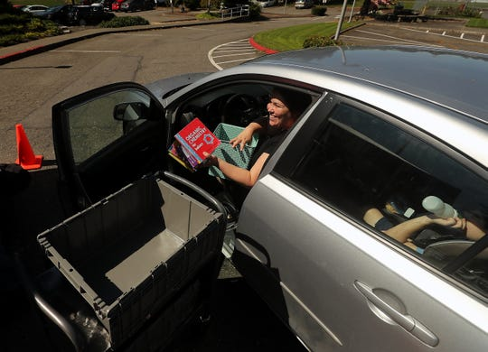 Richelle Masch smiles as she chats with Kitsap Regional Library Sylvan Way branch manager Bert Rinderle while dropping off books that her at the curbside dropoff on Friday. KRL has begun accepting items and will soon allow patrons to place holds on items for curbside pickup.