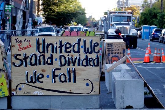 """A sign on a barricade reads """"United we stand divided we fall,"""" as a truck and other heavy equipment from the Seattle Department of Transportation is staged at the the CHOP (Capitol Hill Occupied Protest) zone in Seattle, Friday, June 26, 2020."""