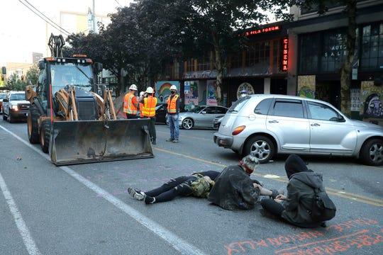 Protesters lie down and sit in the street after workers and heavy equipment from the Seattle Department of Transportation arrived at the the CHOP (Capitol Hill Occupied Protest) zone in Seattle, Friday, June 26, 2020.