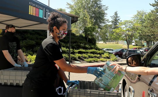 Teen services librarian Nicole Rawlinson collects books curbside at the Kitsap Regional Library Sylvan Way Branch in Bremerton on Friday.