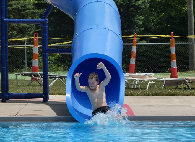 A swimmer enjoys one of the two water slides at Aumiller Park pool on Thursday.