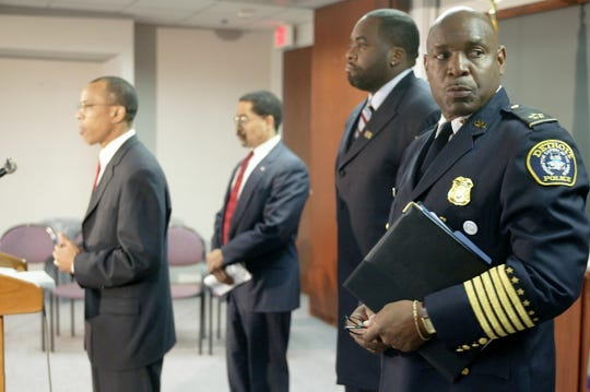 Detroit Police Chief Jerry Oliver, right, looks on during a 2003 press conference as U.S. Attorney Jeffrey Collins announces an agreement on two court-backed consent decrees that will force the DPD to cease practices that led to civil rights abuses. Also pictured are Assistant Attorney General Ralph Boyd and Detroit Mayor Kwame Kilpatrick.
