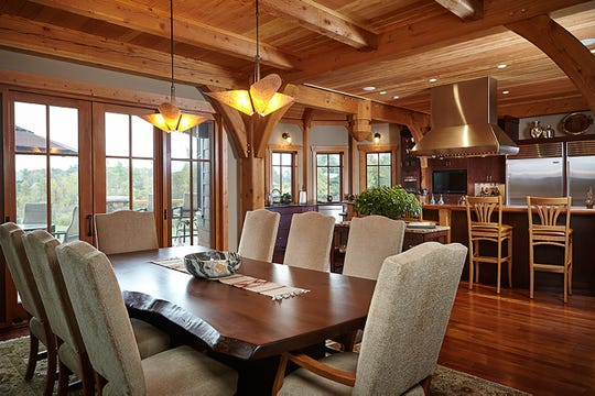 "Dining room and kitchen are open to each other in an area big enough for a party. A raised stone terrace is outside the French doors.  The table is a thick slab of a walnut tree; the bar and cabinets are stained cherry; the floor is Brazilian cherry. ""This is a wood lover's house,"" the owner said. The stunning timber-frame home of 10,000 square feet, on 72 acres of land, uses lots of glass as well as woods to blur the lines of inside and out."