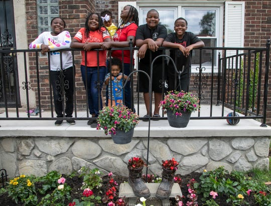 Denise Chandler, 37, of Detroit lost her husband, Richard Chandler when he died March 29 at Sinai-Grace Hospital in Detroit. She poses with six of her eight children behind the memorial garden she planted in his name. Mackenzie Chandler, 8, left,  Kelsey Chandler, 9, Sebastian Ontiveroz, 2, Denise Chandler, 37, (holding) Zoe Ontiveroz, 1, Kodie Chandler, 12, Kaleb Chandler, 10.