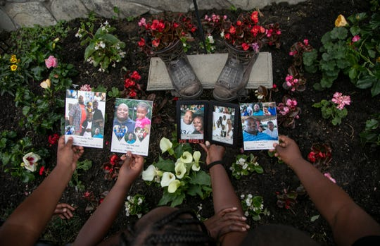 Denise Chandler, 37, of Detroit lost her husband, Richard Chandler when he died March 29 at Sinai-Grace Hospital in Detroit. Denise Chandler holds personalized photos of her late husband with three of her eight children over the memorial garden that includes her husband's work boots.