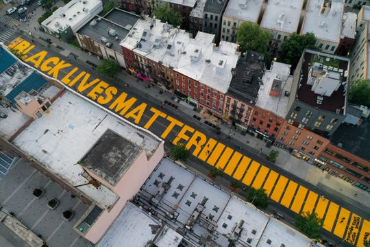 "FILE- In this June 15, 2020, file photo, a sign reading ""Black Lives Matter"" is painted in orange on Fulton Street in the Brooklyn borough of New York."
