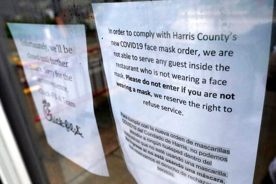 """A sign about the new face mask order is posted on the door of a closed restaurant Thursday, June 25, 2020, in Houston. Texas Gov. Greg Abbott said Wednesday that the state is facing a """"massive outbreak"""" in the coronavirus pandemic and that some new local restrictions may be needed to protect hospital space for new patients."""