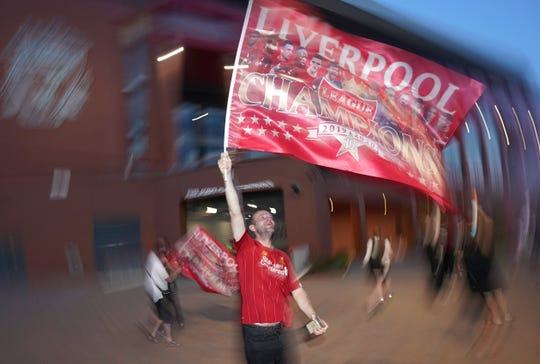 A Liverpool supporter celebrates outside Anfield Stadium in Liverpool, England, on Thursdayafter hearing Chelsea had scored in the English Premier League soccer match between Chelsea and Manchester City.