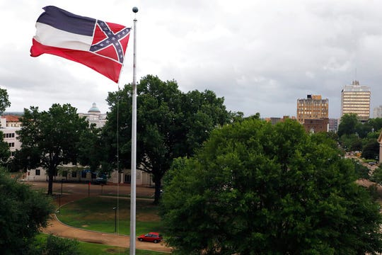 A Mississippi state flag flies outside the Capitol in Jackson, Miss., Thursday, June 25, 2020. Athletic coaches and their staffs from the state's public universities held a joint news conference and called for a change in the Mississippi state flag.