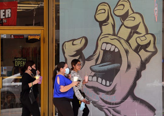 People wearing masks to protect against the spread of COVID-19, pass a mural on a business that has reopened in San Antonio, Wednesday, June 24, 2020, in San Antonio. Cases of COVID-19 have spiked in Texas and the governor of Texas is encouraging people to wear masks in public and stay home if possible.