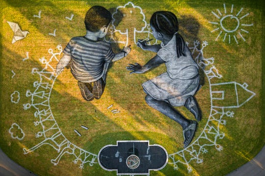 "In this picture made available Friday, June 26, 2020 an aerial view shows a giant ephemeral landart painting by Swiss French artist Saype entitled ""World in Progress"" representing two children drawing their ideal world, at the European headquarters of the United Nations in Geneva, Switzerland, Wednesday, June 24, 2020."