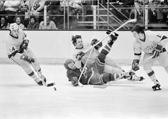 Los Angeles Kings defenseman Dave Hutchison, center, checks John Van Boxmeer of the Colorado Rockies as Syl Apps, left, carries the puck during the first period in Los Angeles on March 2, 1978.