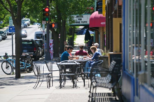 People eat lunch outside at a restaurant in south Minneapolis, Thursday, June 11, 2020, one day after restaurants were given the go ahead for inside dining with occupancy and distancing restrictions due to the coronavirus.