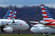 In this March 31, 2020 file photo American Airlines planes are parked at Pittsburgh International Airport in Imperial, Pa.  There will be no more attempt at social distancing on American Airlines flights. The airline said Friday, June 26,  that it will start booking flights to full capacity next week.