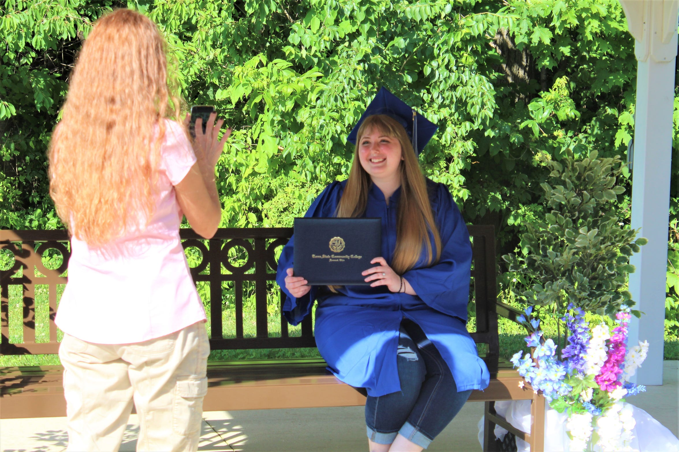 Aubrey Stanforth of Tiffin gets her photo taken with her Terra State Community College diploma Thursday out of the college's Neeley Center. Stanforth was awarded an associate's degree in psychology.