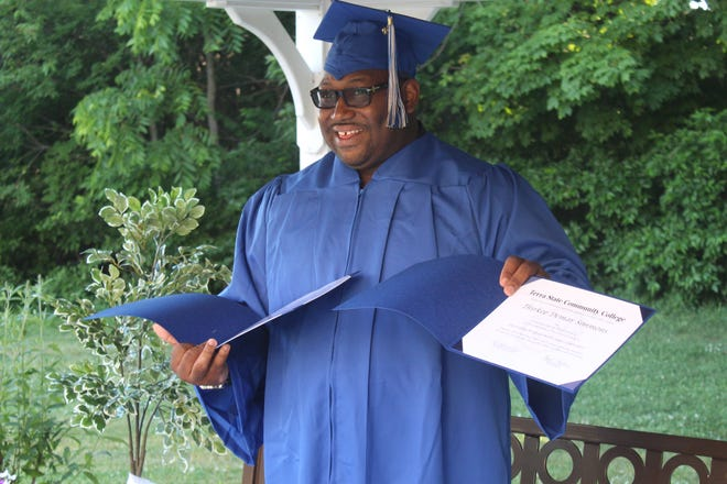 Thirkee Simmons of Sandusky shows off the associate's degree in robotics/integrated manufacturing he earned from Terra State Community College Thursday at the college's commencement ceremony.