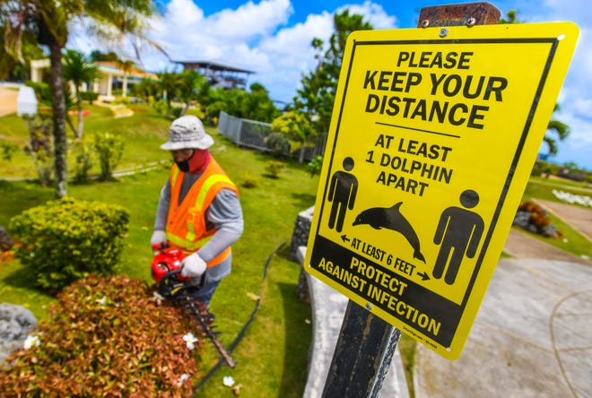 A sign promotes social distancing in this June 26, 2020 file photo, as landscaper Sanjay Kachita works Puntan Dos Amantes, or Two Lovers' Point. Early, and optimistic, estimates predict about 82,000 total visitorson Guam in fiscal 2021. PDN FILE PHOTO