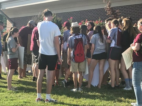 Student athletes gather around to hear a special called school board meeting being live streamed. The group was demonstrating asking for a return to sports practices (June 25, 2020).