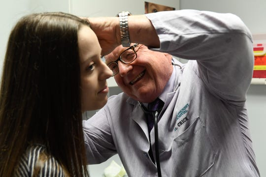 Dr. Larry Crick looks into Ashley Morris' ears during a routine examine Thursday. The local pediatrician is retiring after 39 years, June 18, 2020.