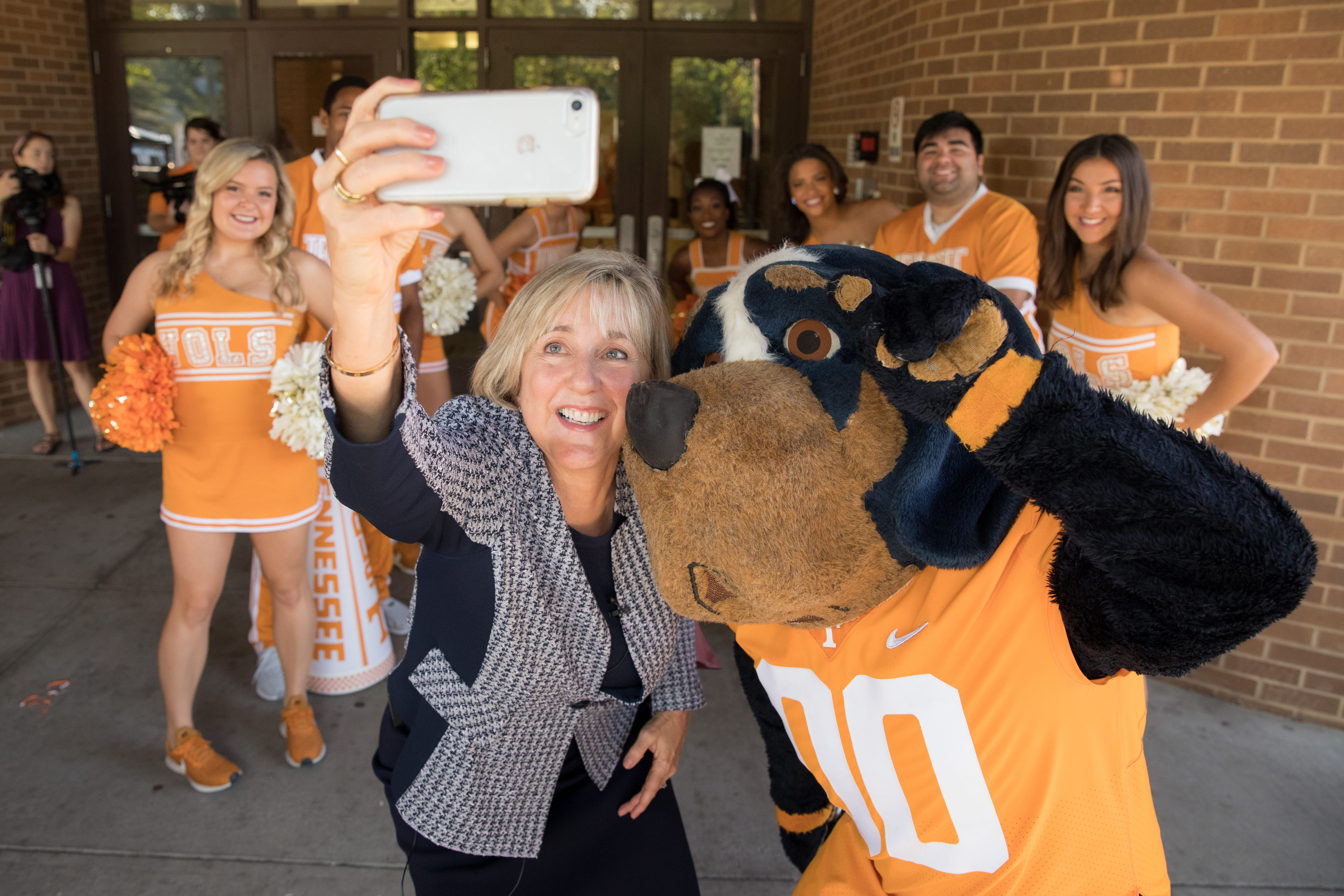Chancellor Donde Plowman poses for a selfie with Smokey and the UT Cheerleaders before surprising West High School students with acceptance letters on Sept. 12, 2019.