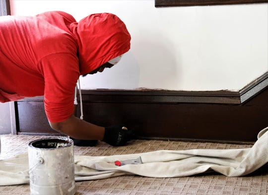 Hakim Washington applies a coat of wood stain to the baseboards of the Allen Chapel Church sanctuary Wednesday, June 24. Led by members of the congregation, repairs and renovations are being done throughout the church. Once the plaster on the walls is sanded down, there will be another coat of paint applied.