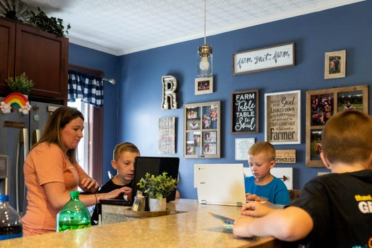 From left, Jamie Raymond and her sons Caleb, 10, Jacob, 5, and William, 9, work on their computers Friday, June 26 at their Conway Township home, which has a spotty internet connection.