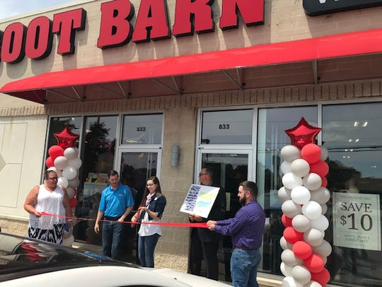 Jodie Perry, Chamber of Commerce president,  left, welcomes Boot Barn management to Ontario on Friday during the official grand opening ceremony at 833 Lexington-Springmill Road.
