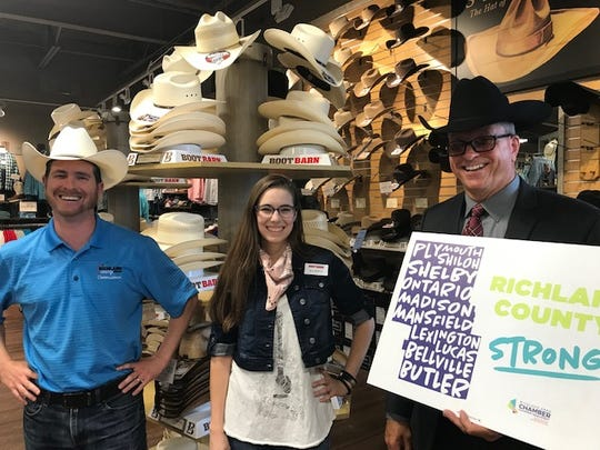 The Boot Barn at 833 Lexington-Springmill Road  in Ontario celebrated a grand opening and ribbon cutting with Chamber of Commerce officials Friday. At left, Richland County Commissioner Tony Vero is joined by Allison Stover, assistant store manager, and Ontario Mayor Randy Hutchinson. The local officials tried on some cowboys hats at the urging of media.