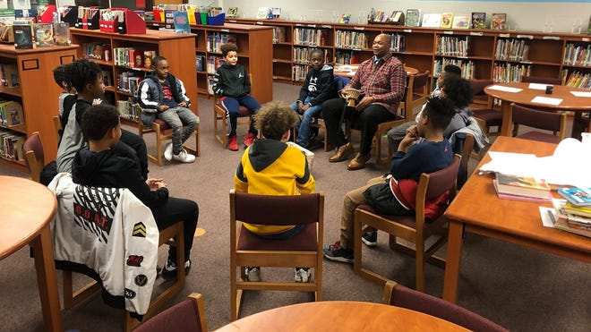 """Johnnie Jackson, equity and diversity supervisor for Marion City Schools, talks with students in one of the district's Harambee groups. Harambee (which means """"all pull together"""") focuses on experiences of African American males and culturally affirming them in school. He brings in literature, multi-media content, and speakers, to make them feel that school is a place where they are accepted and affirmed."""