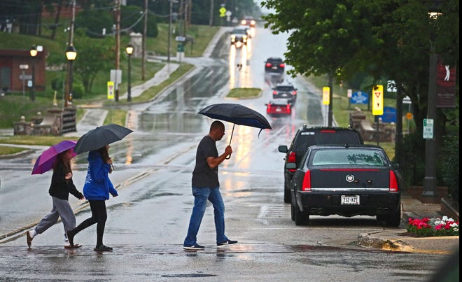A family dashed across Milwaukee Street in the rain as they headed to a restaurant in downtown Delafield.