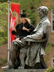 A University of Wisconsin-Madison graduate poses for a picture on the statue of Abraham Lincoln on Bascom Hill in 2008.