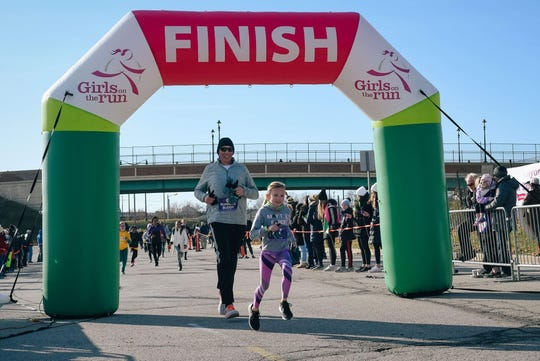 Jason and Cailin Grusnick cross the finish line at a Girls on the Run race in November 2019.