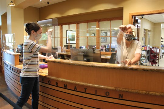 Members of the Baxter County Library staff set up plastic glass dividers atop the library's circulation desk. The dividers were purchased with a purchased with a grant from the Arkansas Community Foundation.