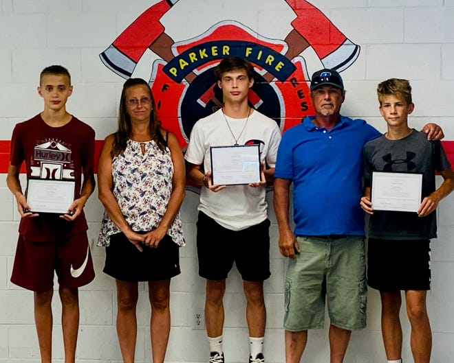 Teens Preston Erwin and Joseph and Easton Foster are presented with the Parker City Volunteer Fire Department's Citizen Hero Award.